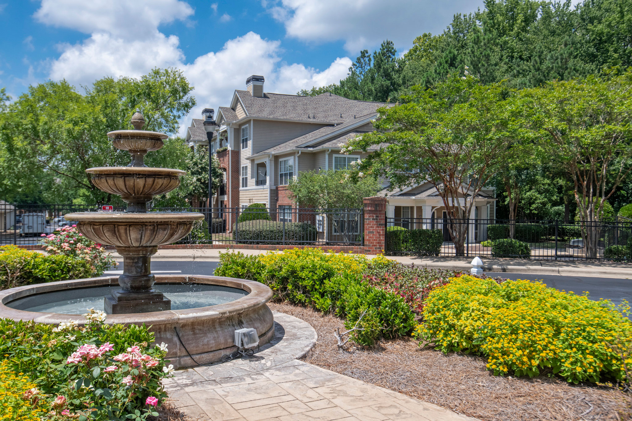 water fountain in front of multifamily building with trees